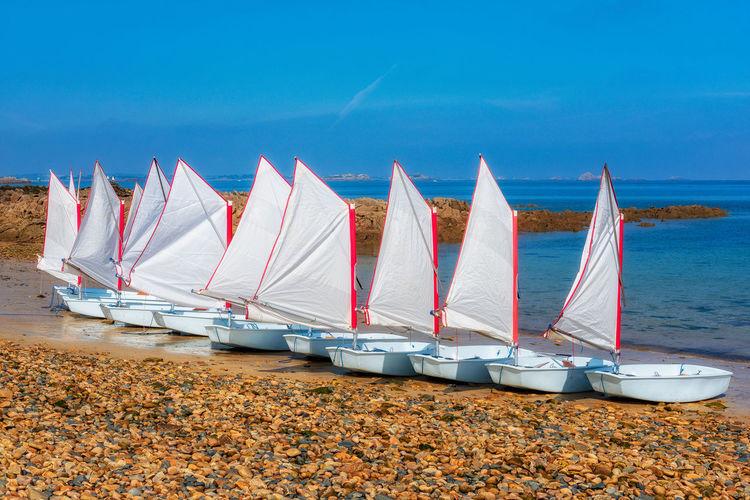 Sailboats moored on beach against blue sky