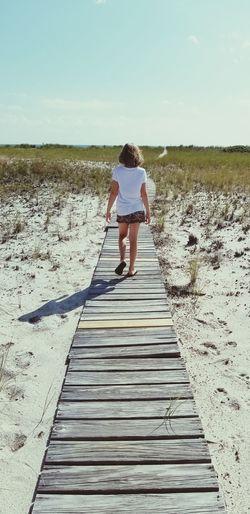 Rear view of girl walking on boardwalk against sky