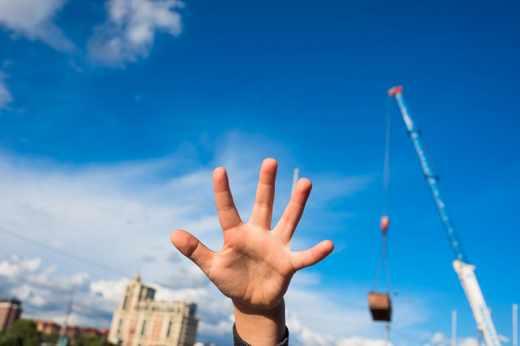 Close-up of hand against blue sky