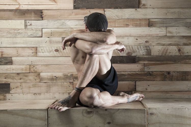 Full length of shirtless young man sitting against wooden wall