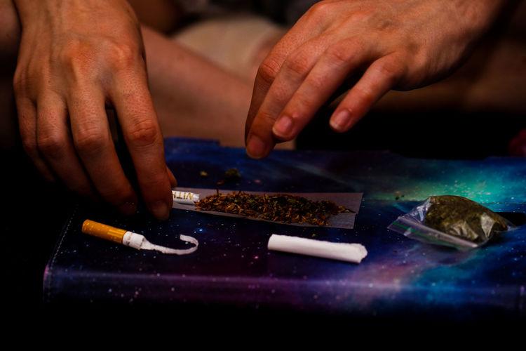 Hands of man making marijuana joint