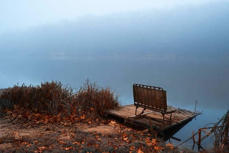 Bench on jetty by lake against sky during foggy weather