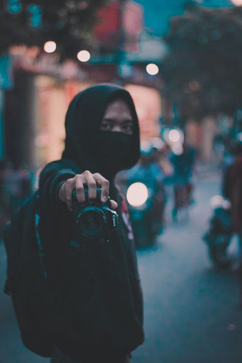 Portrait of man photographing illuminated street at night