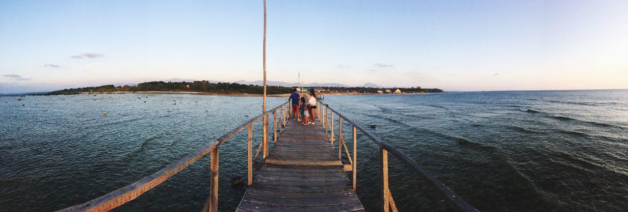 Family on pier over sea against sky