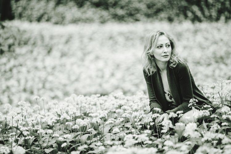 Beautiful Woman Sitting Amidst Flowers On Field