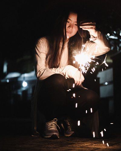 Young woman holding illuminated sparkler while crouching at night