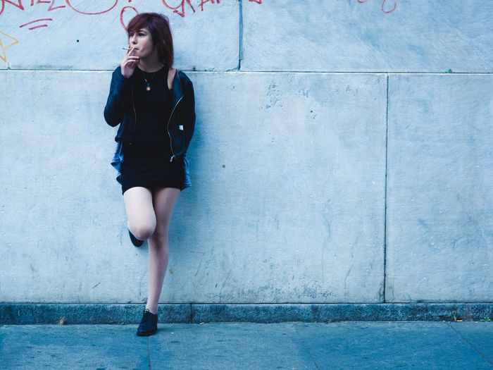 Casual Clothing Day Fashion Fashionable Footpath Front View Full Length Girl Legs Person Shoe Smoking Wall Young Adult