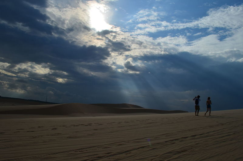 Rear view of couple walking at desert against cloudy sky