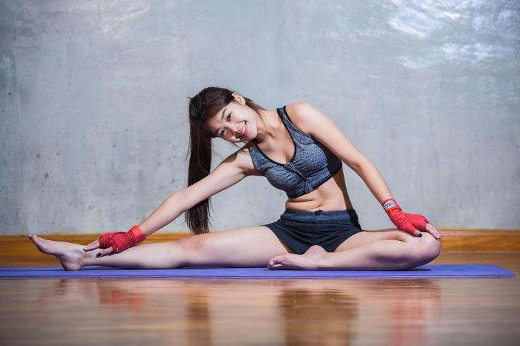 Young woman exercising against wall