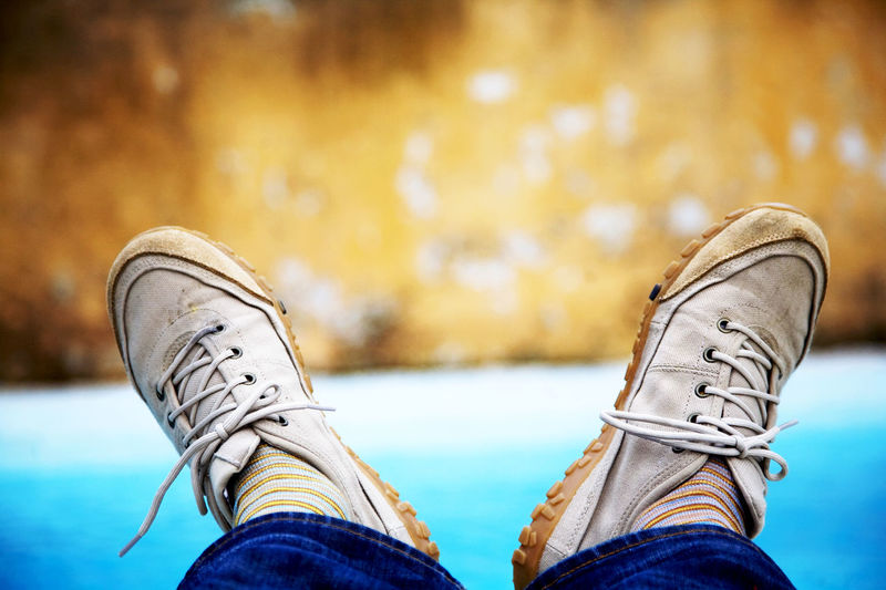 Man with his feet up by a swimming pool. Canvas Shoe Close-up Day Horizontal Human Feet Jeans Lifestyles Looking Down Low Section Outdoors Personal Perspective Relaxation Rolled Up Pants Shoe Shoelace Water