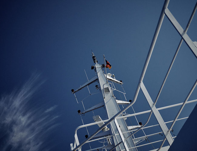 Low angle view of radar on boat against blue sky