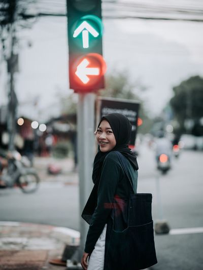Portrait Of Smiling Woman Standing On Road In City