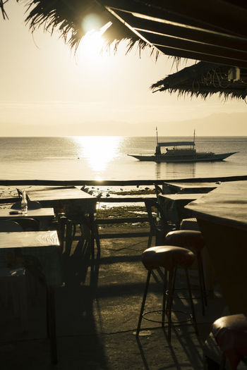 Empty chairs and table against sea during sunset