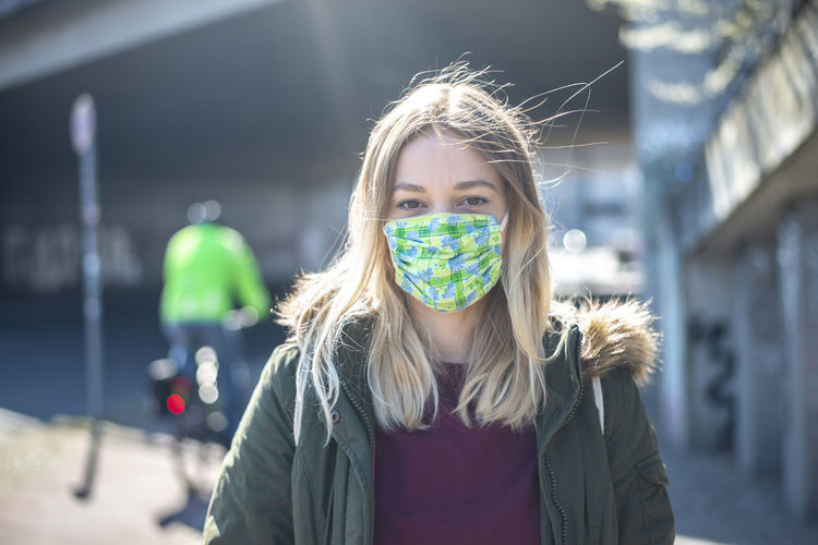Sick young woman wearing mask standing in city