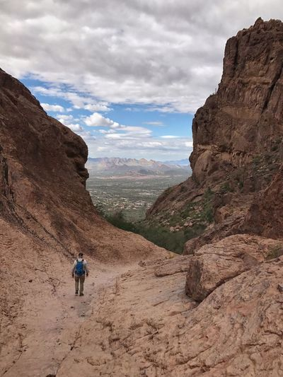 Rear view of man walking on rocky mountain against cloudy sky