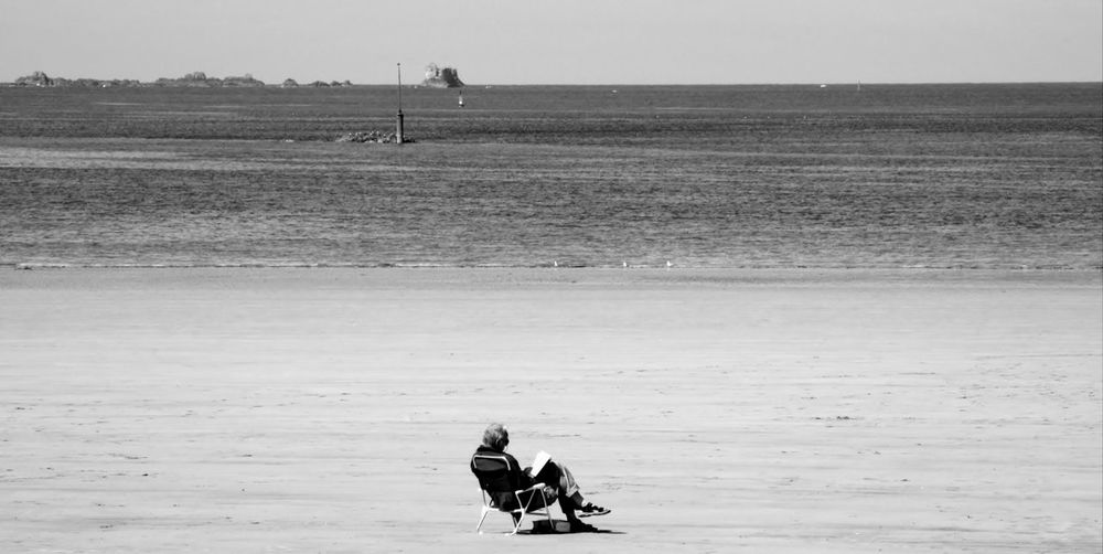 Black and white image of old man  reading book at beach