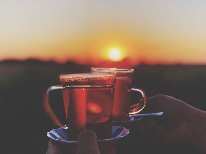 Cropped hands holding black coffee cup against sky during sunset