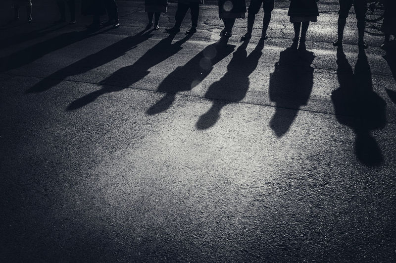 Shadows on the pavement, group of people standing on the street aligned, casting long shadows on asphalt sidewalk. Abstract Aligned Alignment Asphalt Black & White Casting Shadows Copy Space Crowd Group Group Of People Long Order Pavement People Road Shadow Sidewalk Silhouettes Spooky Standing Street Unrecognizable Urban