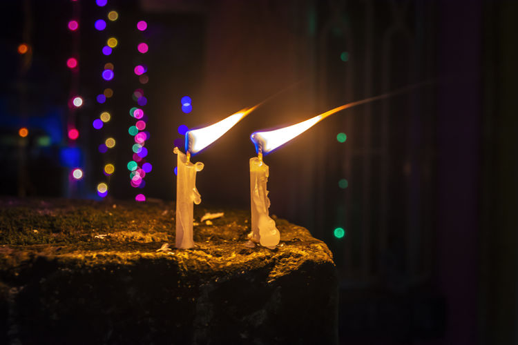 Close-up of lit candles on stone during night