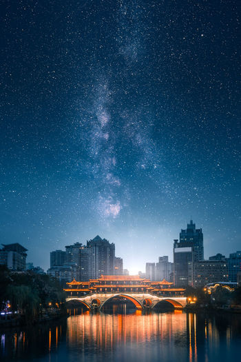 Illuminated bridge over river with buildings in background against star field