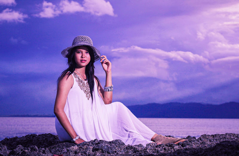 Portrait of young woman sitting against sea against sky against sunlight