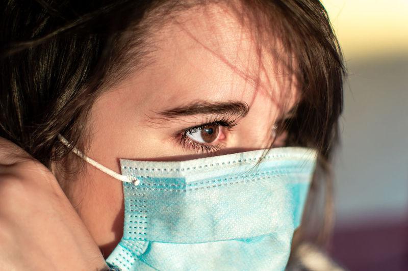 Close-up of beautiful woman wearing flu mask outdoors