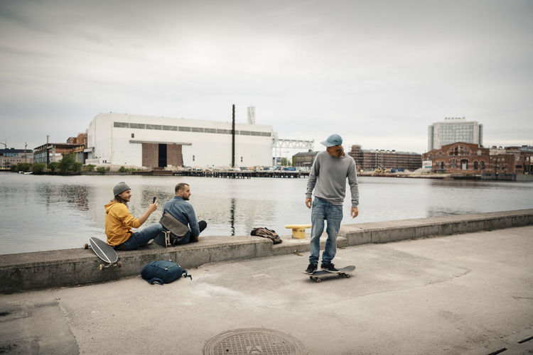 People sitting on riverbank against sky in city