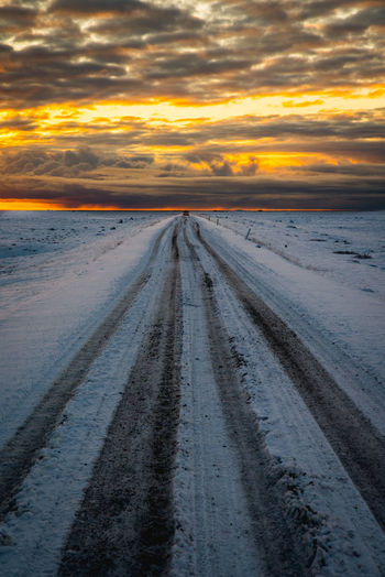 Tire tracks on road during sunset