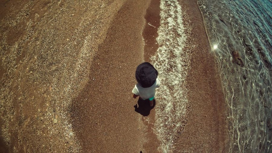 Directly Above Shot Of Boy Standing On Wet Shore