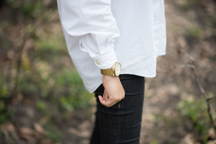 Midsection of man wearing wristwatch while standing on land
