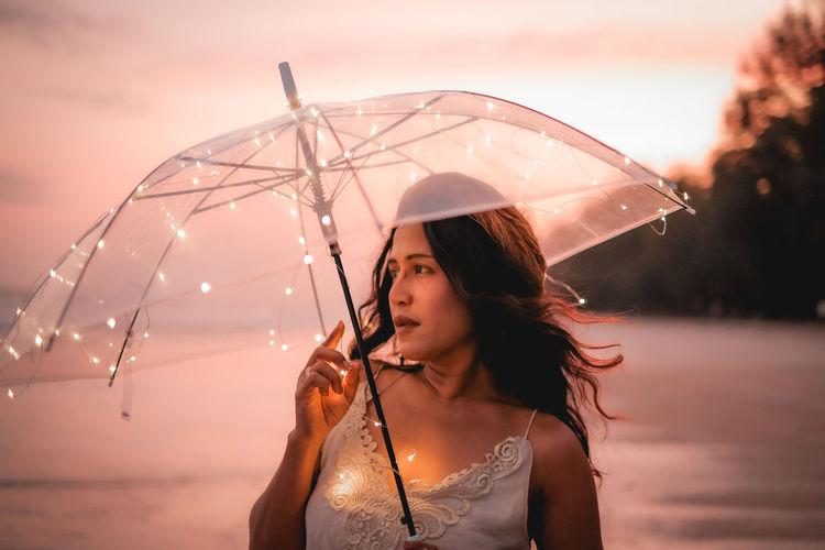Portrait of woman holding wet umbrella