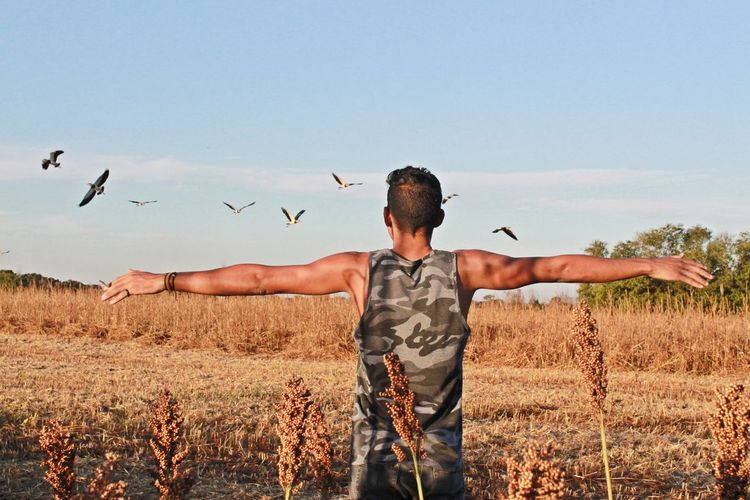 Rear view of man with arms outstretched standing on land