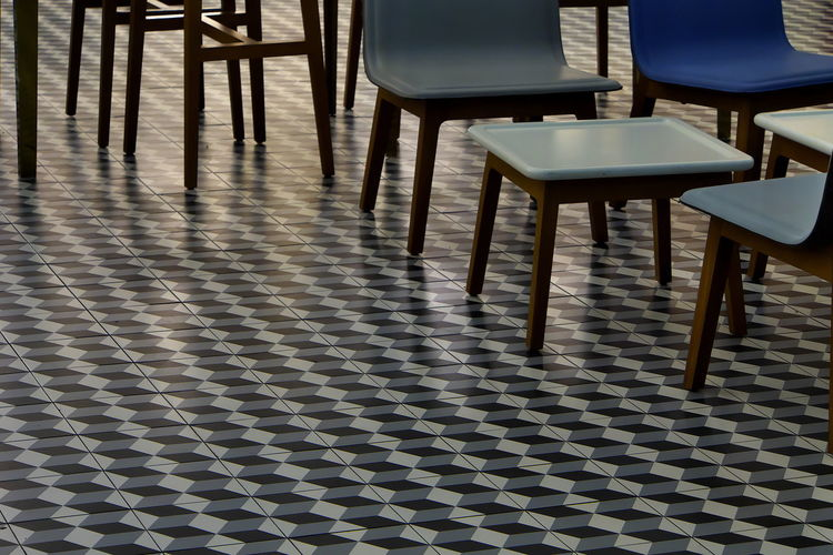 Close-up of chairs and table on tiled floor