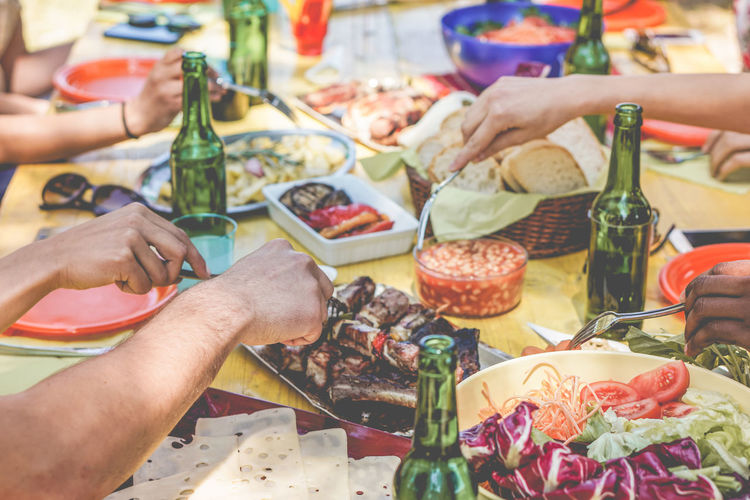 Hands view of diverse culture friends eating bbq dinner outdoor BBQ Beer Dinner Friends Hands Picnic Salad Barbecue Celebrating Drink Eating Food Freshness Grill Group Lifestyles Meal Meat Men Outdoor People Salad Summer Table Vegetable