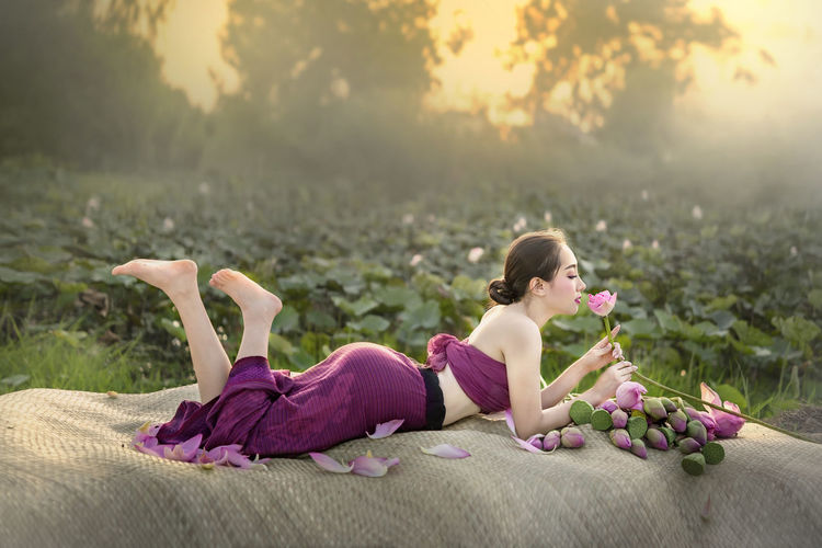 Full length of beautiful woman resting on textile with lotus flowers on land