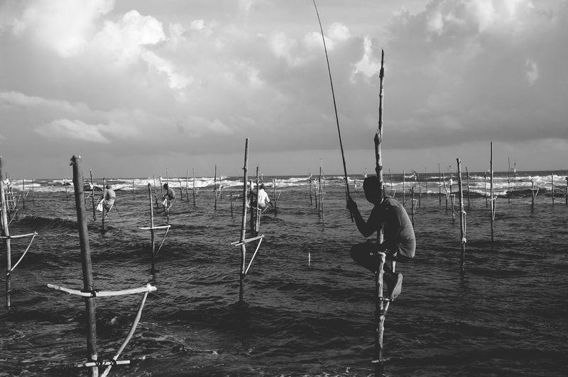 Men stilt fishing amidst sea against cloudy sky