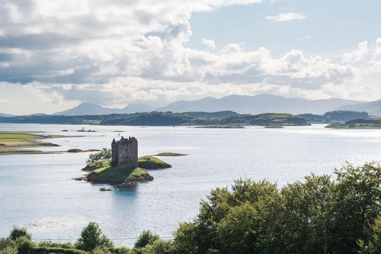 Castle Stalker In Lake Against Sky