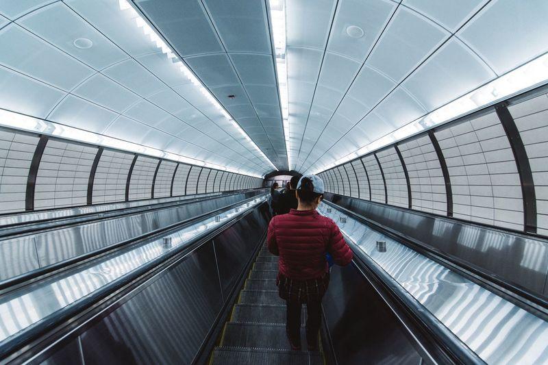 Rear view of woman on escalator at subway station