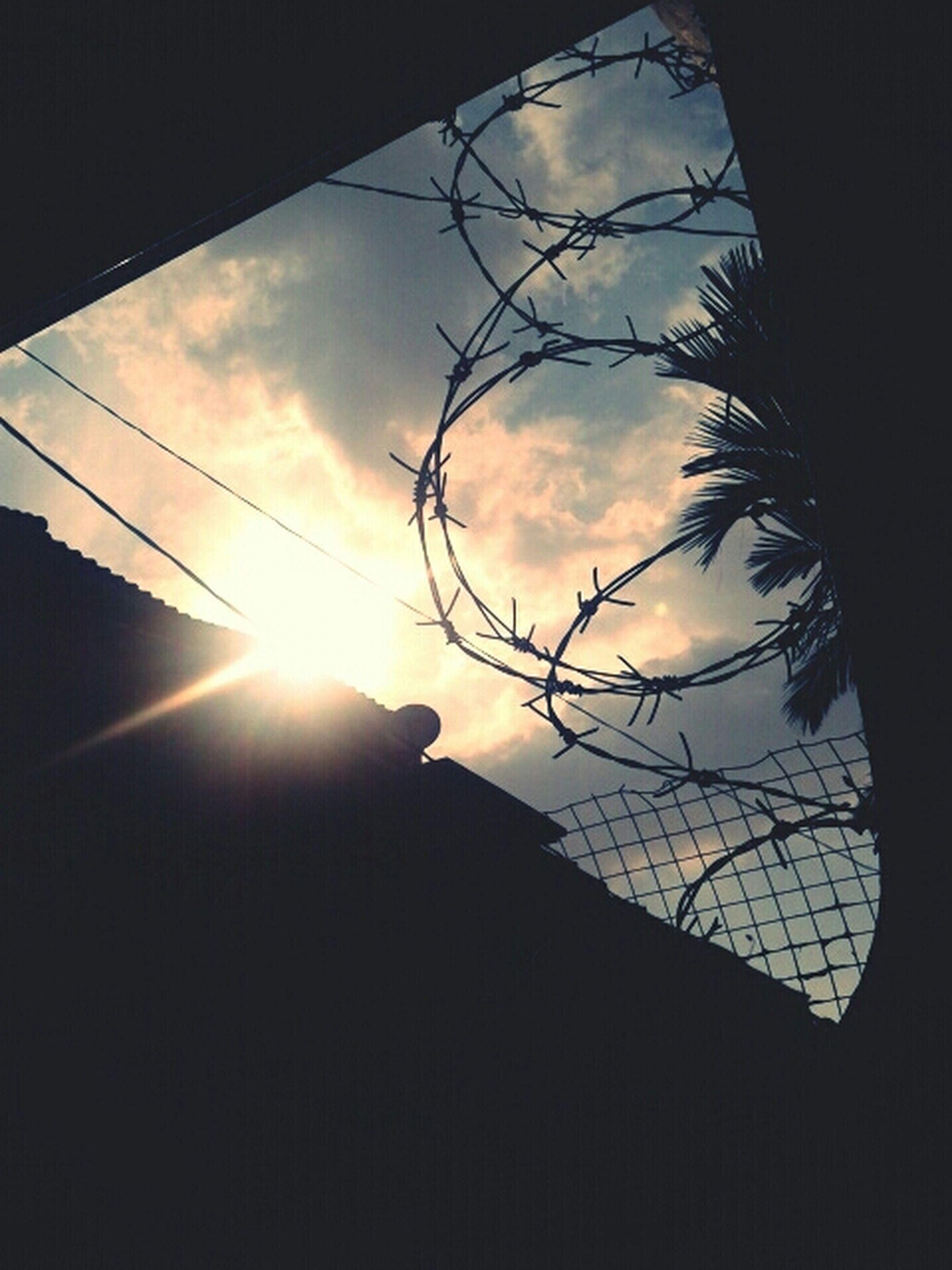 silhouette, low angle view, sun, sky, sunset, built structure, architecture, sunlight, cloud - sky, sunbeam, building exterior, power line, nature, lens flare, electricity, cloud, no people, outdoors, electricity pylon, cable