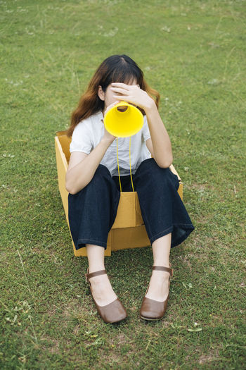 Full length of woman sitting in cardboard box