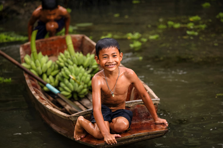Portrait of shirtless boy sitting on boat in river