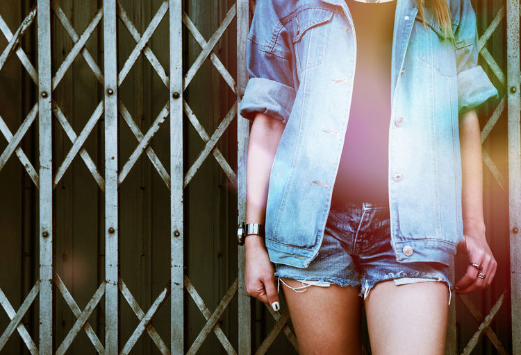 Midsection of woman wearing denim jacket standing against gate