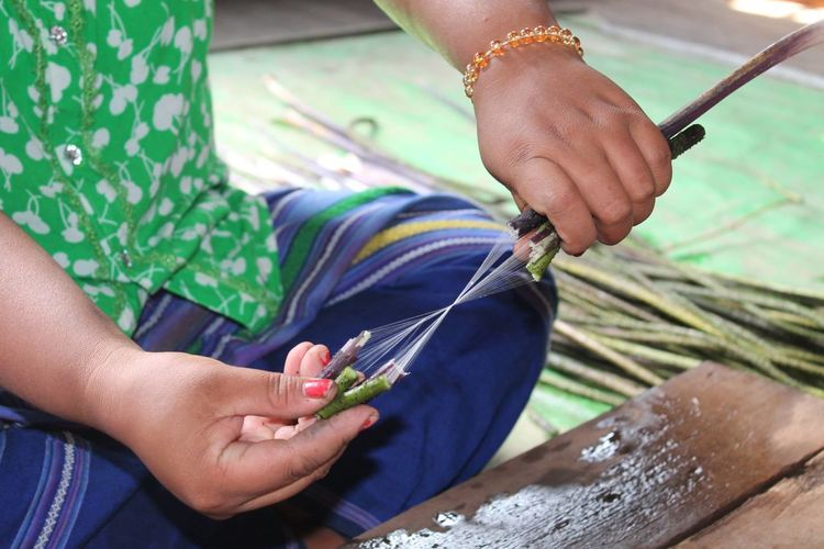 Midsection of woman extracting and weaving lotus fibers