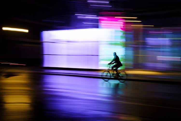 Blurred motion of man cycling at illuminated city