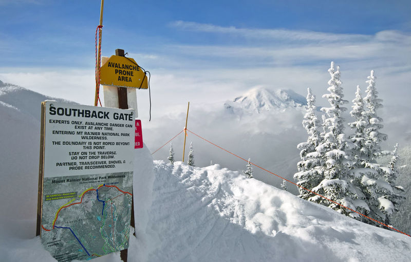 Information sign on snowcapped mountain against sky