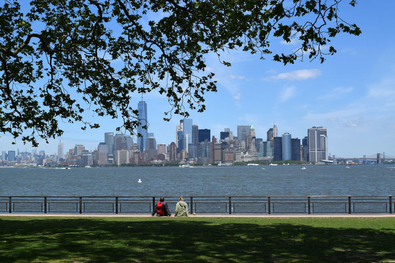 Rear view of people sitting at park by hudson river and city skyline against sky