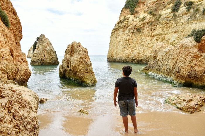 Alone in the beach Young Boy Boy Rear View Alone... Alone On The Beach Water Sea Beach Men Adventure Sand Full Length Standing Rear View Rock - Object Geology Rock Formation Hiker Natural Arch Physical Geography Ankle Deep In Water Natural Landmark