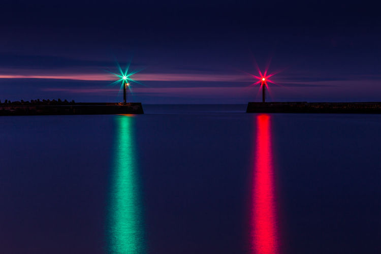 Illuminated lights reflecting on sea against sky at night
