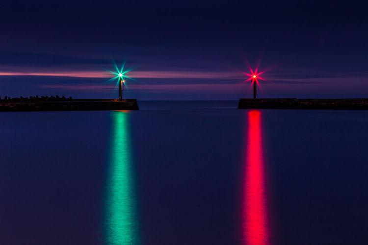 Illuminated Lights Reflecting On Sea Against Sky At Night