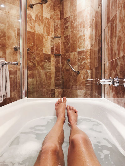 Low section of person legs in bathroom at home